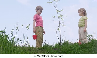 boy with bucket and girl with shovel takls about young plant