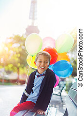 Boy with bunch of colorful balloons in Paris near the Eiffel tower.