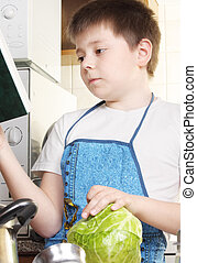 Boy with cabbage looking to cookbook