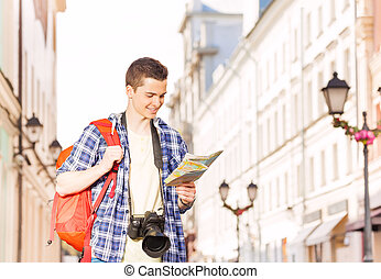 Boy with camera and city map on the street