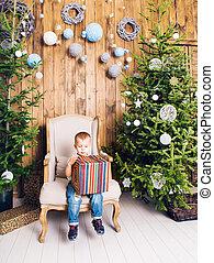 Boy with christmas gift near Christmas tree