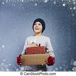 Boy with christmas present among snow falling