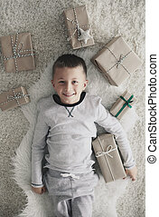 Boy with christmas present lying on back