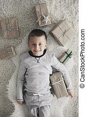 Boy with christmas present lying on back