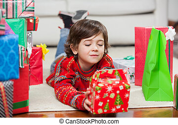 Boy With Christmas Present Lying On Floor