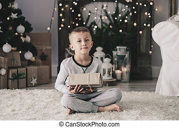Boy with christmas present sitting on rug