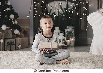 Boy with christmas present sitting on rug