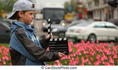 Boy with cinema clapper board hands stands on streets - boy...