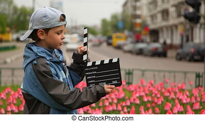 Boy with cinema clapper board is on city streets