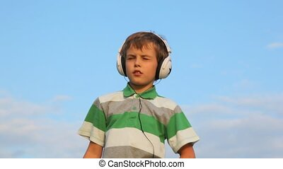 boy with closed eyes listen to music through headphones and...