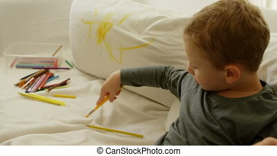 Boy with color pencil on sofa 4k - Boy with color pencil on...