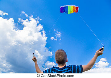 Boy with colorful kite against blue sky