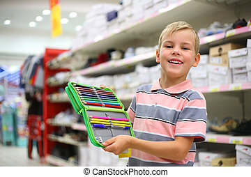 Boy with colour pencils in shop