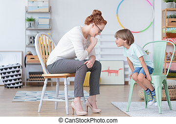 Boy with counselor in classroom - Young boy sitting on mint...