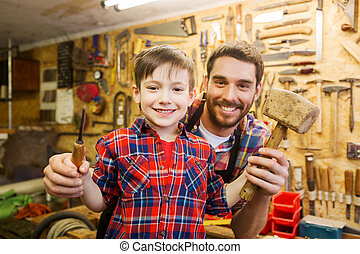 boy with dad holding chisel and hammer at workshop - family,...