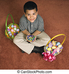 Boy with Easter baskets. - Hispanic boy sitting on floor...