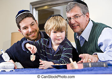 Boy with father and grandfather spinning dreidel,...