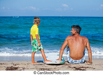 Boy with father surfing