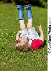Boy With Feetup Laughing While Lying On Grass