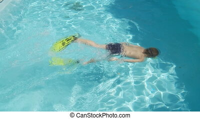 boy with fins snorkeling in swimming pool