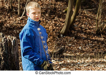 Boy with fishing rod with copy space over leaves