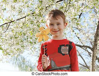 Boy with flower under spring tree