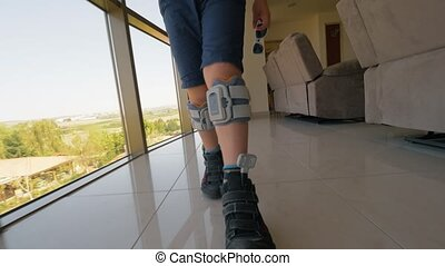 Boy with foot drop system walking indoor - Steadicam shot of...