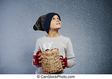 Boy with gift box looking at snow