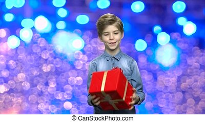 Boy with gift box on Christmas background. Adorable child...