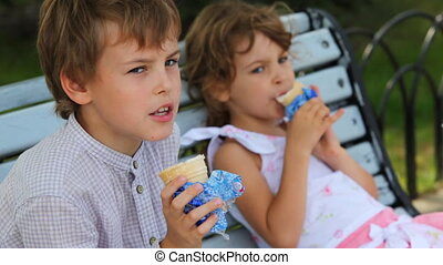 boy with girl eat ice cream and sit on bench at park