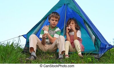 boy with girl have a rest, sitting under tent and eating cakes