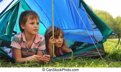 Boy with girl lay peeping out of tent, he something says at forest