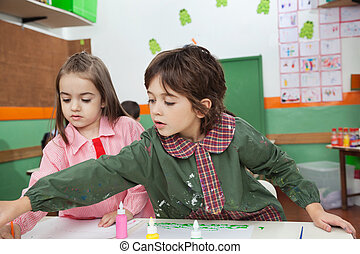 Boy With Girl Painting At Classroom Desk