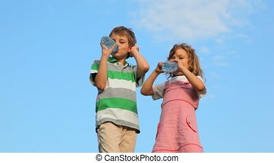 boy with girl standing and drink water from plastic bottles