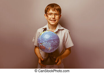boy with glasses holding a globe