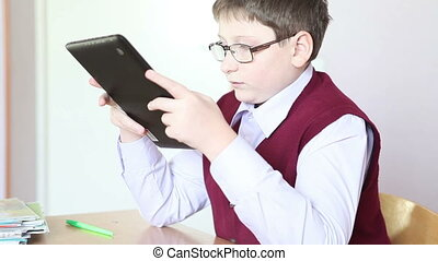 boy with glasses playing the tablet at school