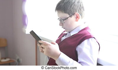 boy with glasses plays on the tablet