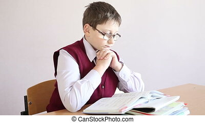 boy with glasses reading a book