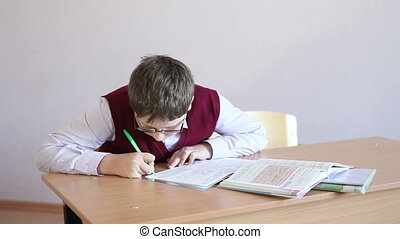 boy with glasses writes in a notebook