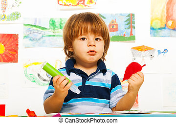 Cute little 2 years old boy in the art glue color paper leaf