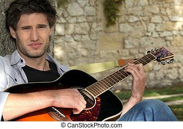 Boy with guitar sitting in garden