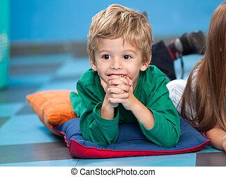 Boy With Hands Clasped Lying On Floor In Kindergarten -...