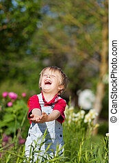 Boy With Hands Cupped Laughing In Yard