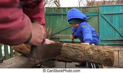 Boy with handy craftsman cutting a log with a two man...