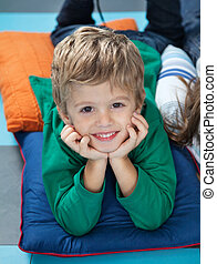 Boy With Head In Hands Lying On Cushions In Kindergarten -...