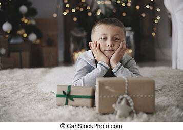 Boy with head in hands lying on floor and dreaming