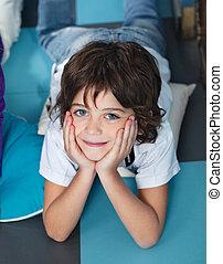 Boy With Head In Hands Lying On Floor In Preschool -...