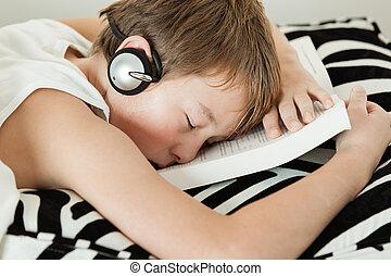 Boy with headphones asleep on top of textbook