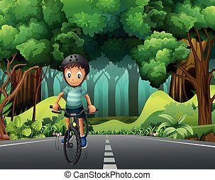 Boy with helmet riding bicycle on the road