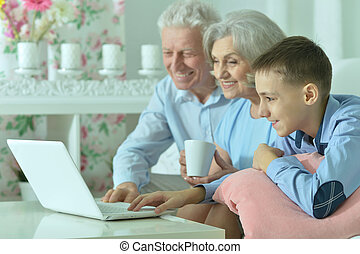 Boy with his grandparents and laptop